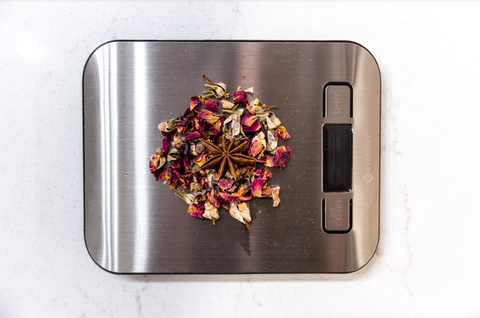 A food scale with a handful of loose tea leaves.