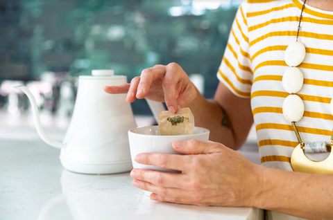 A woman sits at a counter and steeps tea with a tea bag.