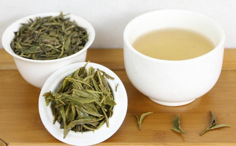 A cup of white tea sits beside two other cups fills with tea leaves.
