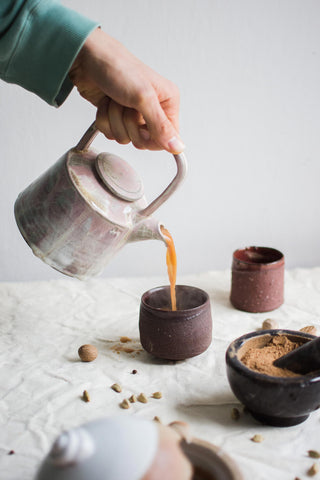 pouring authentic chai tea into a cup
