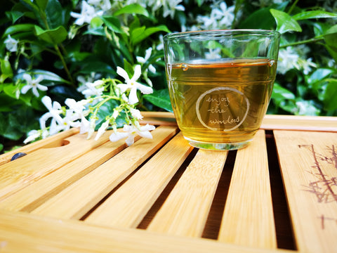 A clear cup of hot tea sits on an outdoor table next to some flowers.