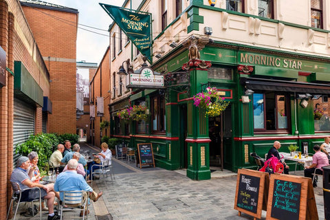 Diners enjoy a meal at an outdoor cafe on Pottinger's Entry, one of the historic, narrow passageways in Belfast, Northern Ireland.