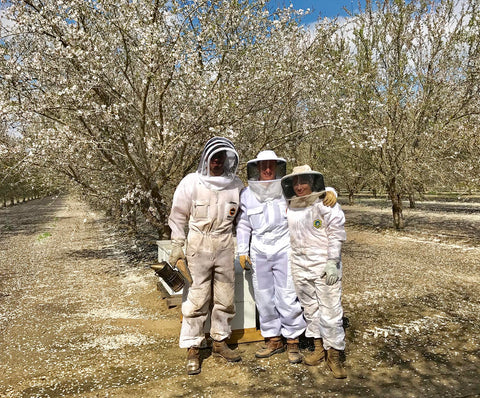 melissa, jeremiah, and joseph register working in the almond grove wearing bee suits and surrounded by almond trees with white blossoms
