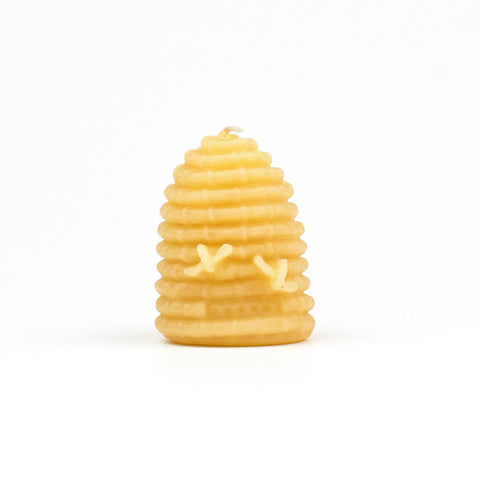 Small skep hive beeswax candle with honey bees.