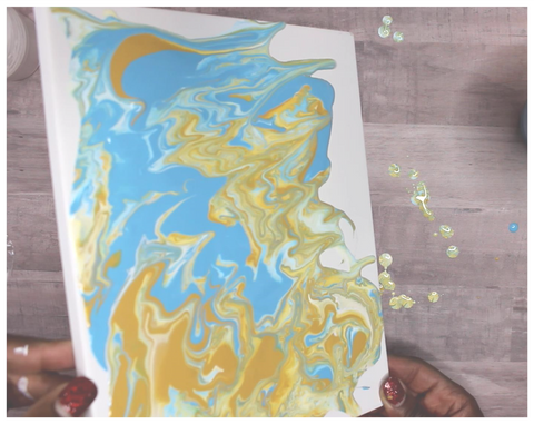 spreading paint for DIY acrylic pour painting