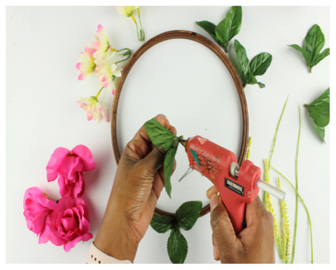 glue gun and flowers for embroidery hoop wreath