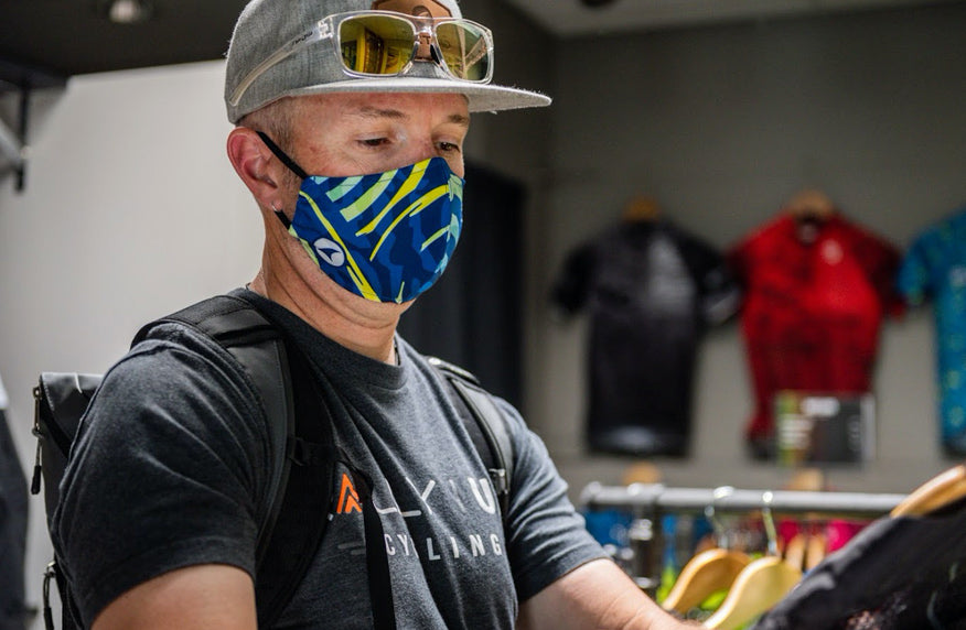 Man wearing a custom printed face mask in a cycling clothing store