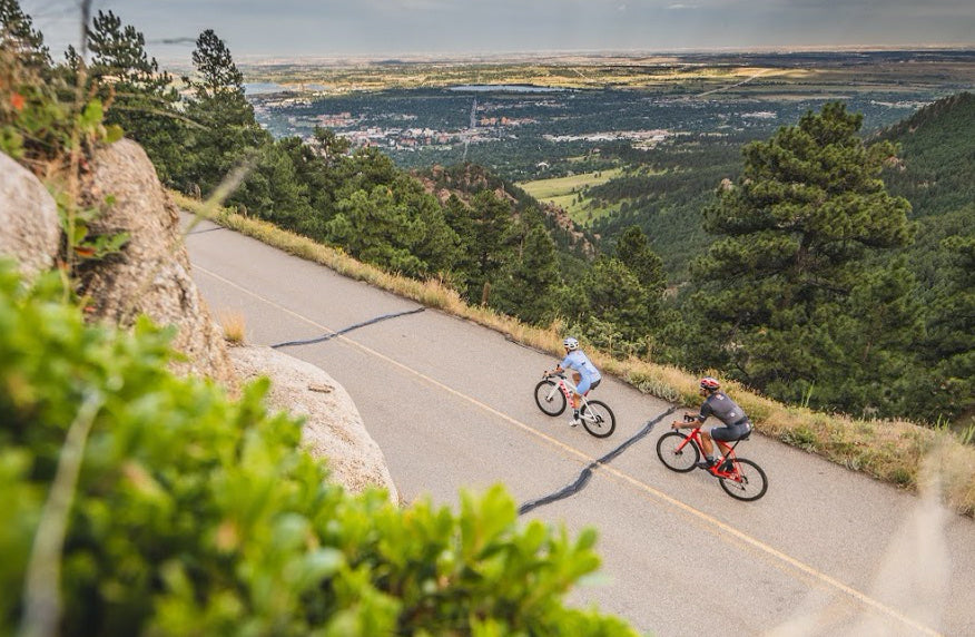 Male and female cyclist riding uphill near Boulder, Colorado