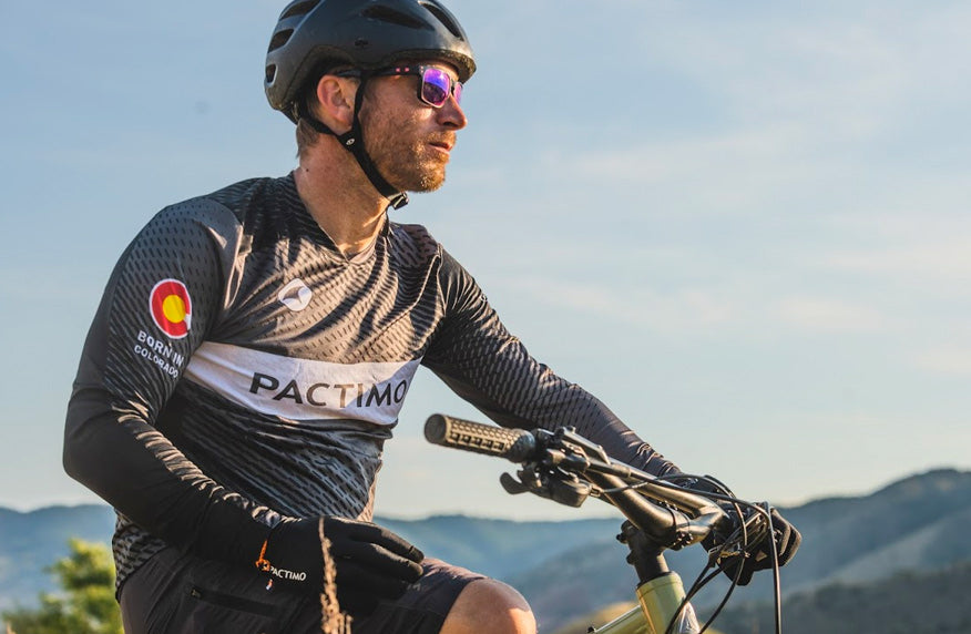 Mountain biker wearing the customizable long sleeve Tellus Jersey