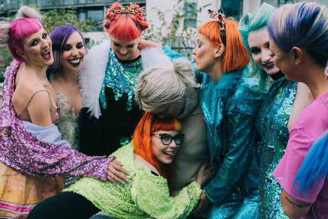 Group of friends cuddling while wearing Isolated Heroes sequins