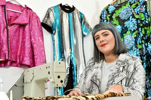 fashion designer Samantha Paton sits behind sewing machine in the Isolated Heroes design studio in Scotland