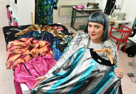 Designer Samantha Paton stands in her fashion design studio with her latest collection