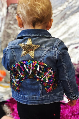 Baby wears customised denim jacket by Isolated Heroes with their name embroidered on the back