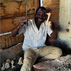 smiling malawian artisan wood carver displaying an ostrich he is working on