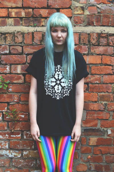 An alt girl with blue hair, wearing a black t-shirt, with a white mandala design and rainbow coloured leggings standing against an orange brick wall