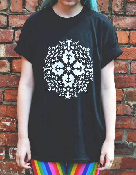 A close up of a girl wearing a black t-shirt with a white mandala design