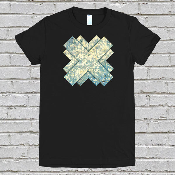 A womens black t-shirt with a cross design, against a white brick wall background
