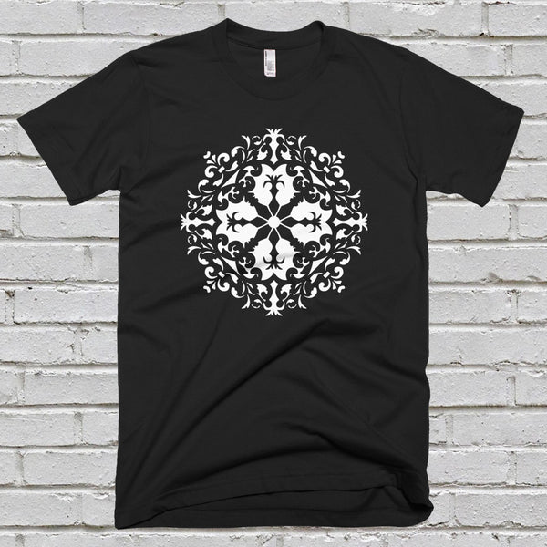 A men's black t-shirt with a white mandala design, against a white brick wall background.