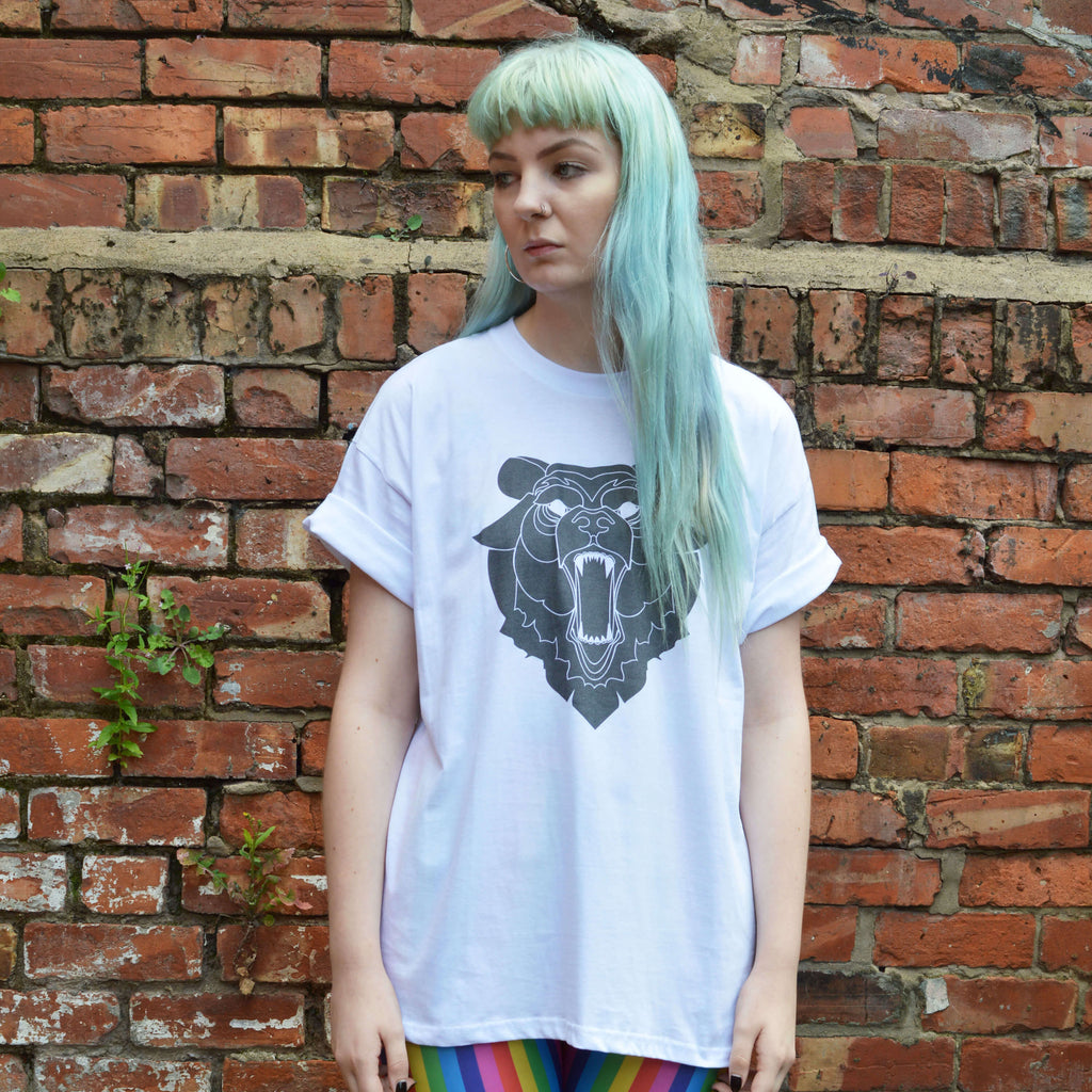 Alternative girl with electric blue hair wearing a white t-shirt with a printed grizzly bear design.