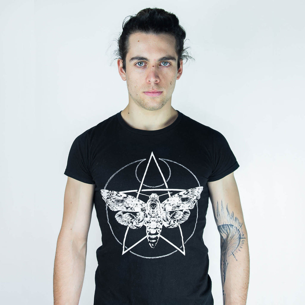 Studio photography of a male model with a tattoo on his arm wearing a death's-head hawkmoth t-shirt.