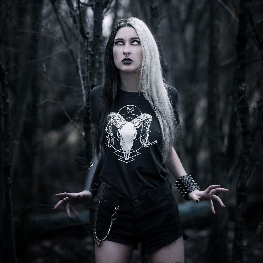 Gothic model Mellifère Hammamélice stood in a dark forest wearing an alternative ram skull t-shirt.