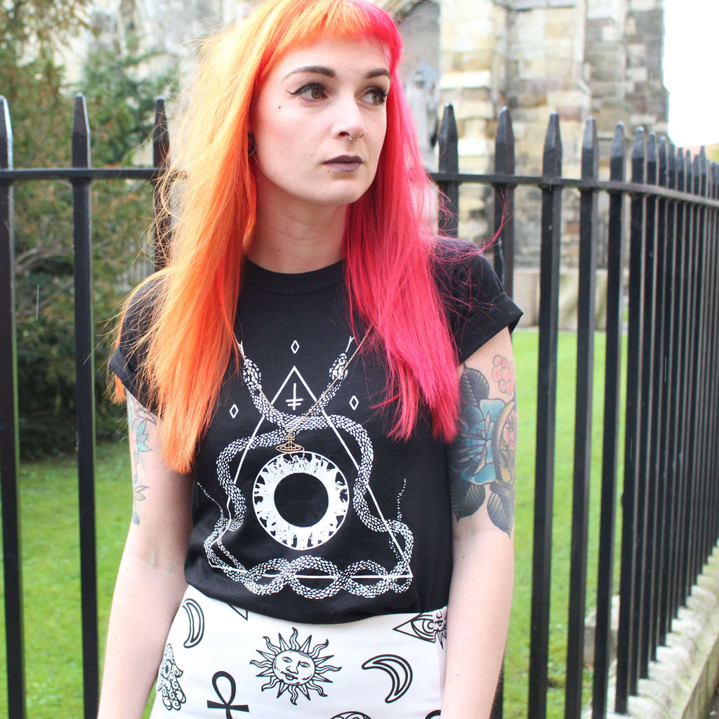 Alternative blogger with red and orange hair wearing a snake t-shirt standing next to a church.