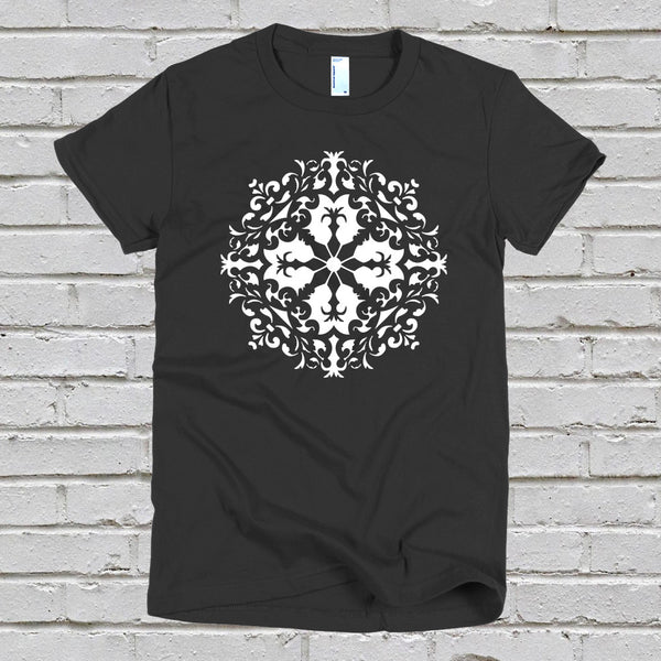 A women's black t-shirt with a white mandala design, against a white brick wall background.