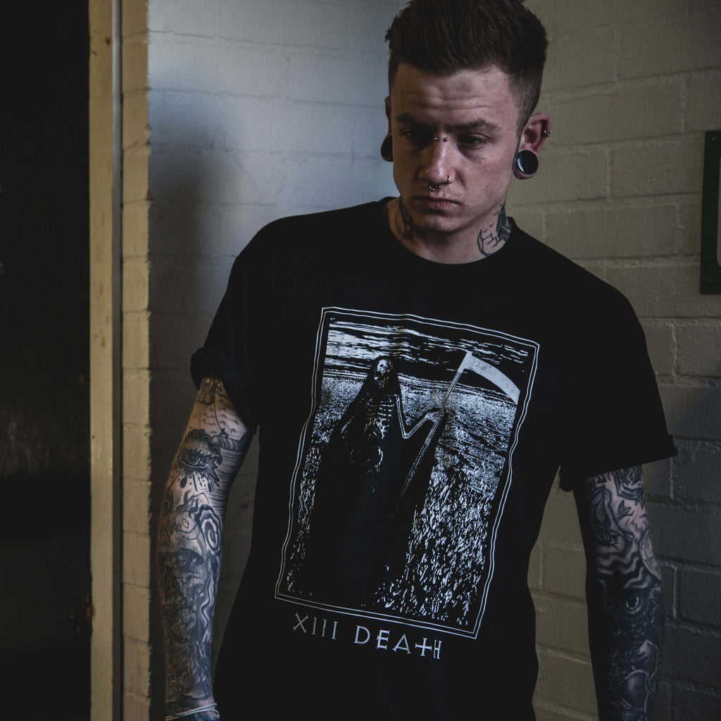 Alternative male model Harry Osmond, covered in tattoos wearing a black death tarot card t-shirt.