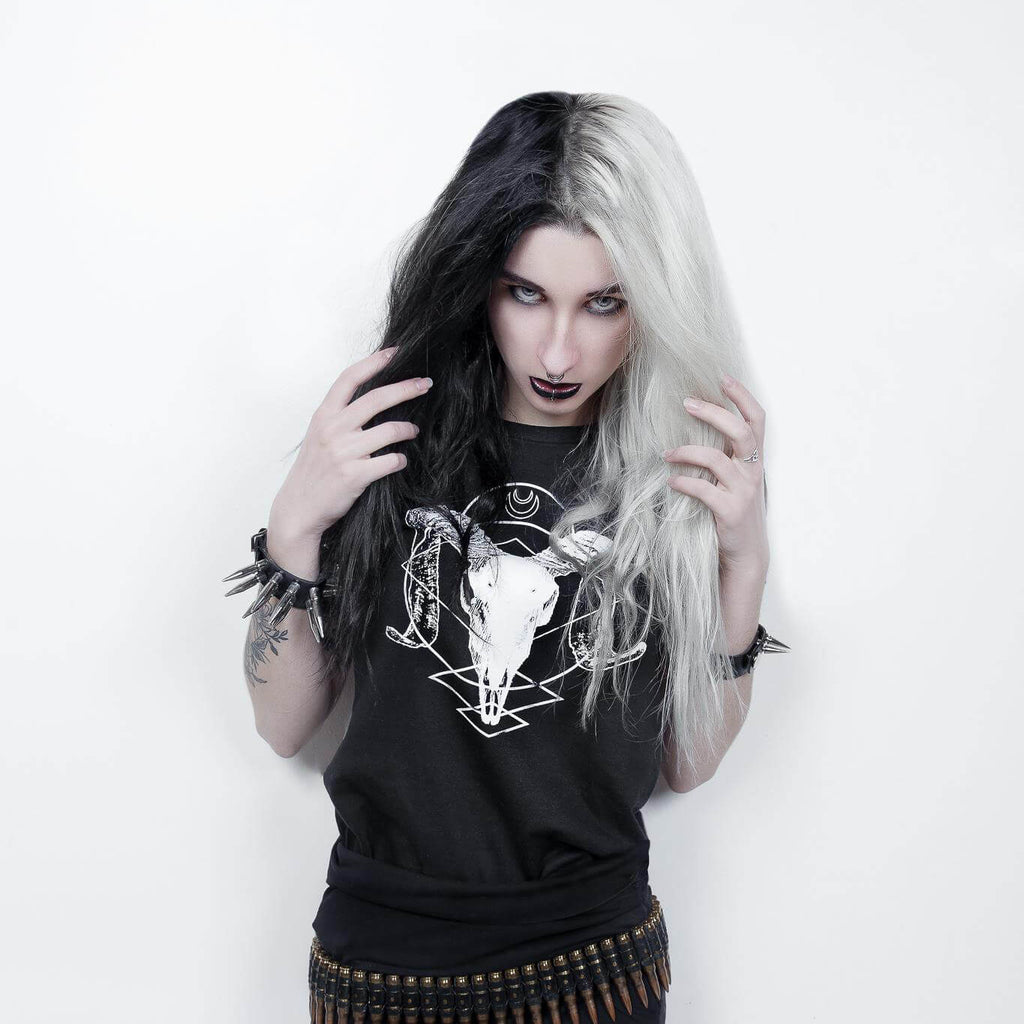 Goth girl Mellifère with half black and half white hair wearing an alternative ram skull t-shirt.