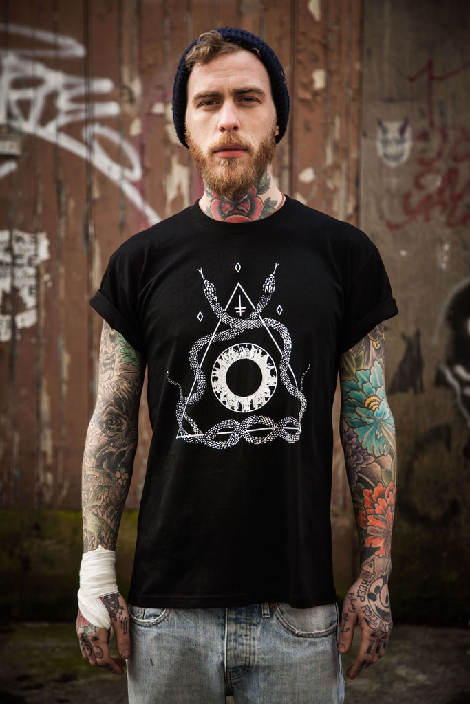 An alternative male model with a ginger beard and tattoos wearing a black snake t-shirt.
