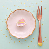 Enamel pin of a slice of cake with layers of pastel colors, shown on a white plate surrounded by gold stars.