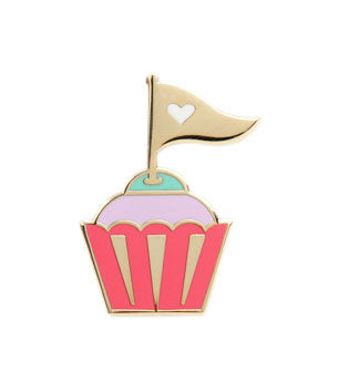 Enamel pin of a colorful cupcake decorated with a gold flag featuring a white heart in the center.