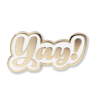 "Enamel pin of the word ""Yay!"" in shiny gold against a white background."