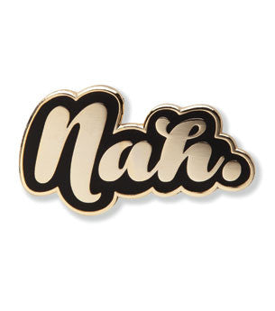 "Enamel pin of the word ""Nah"" in shiny gold against a black background."