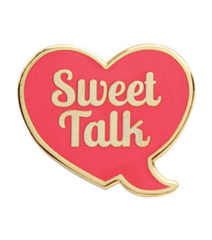 Enamel pin of a heart shaped conversation bubble with the words 'Sweet Talk' inside.