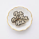 "A white dish with a pile of several enamel pins of the word ""Nah"" in shiny gold against a black background."