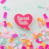 Enamel pin of a heart shaped conversation bubble with the words 'Sweet Talk' inside shown surrounded by colorful confetti.