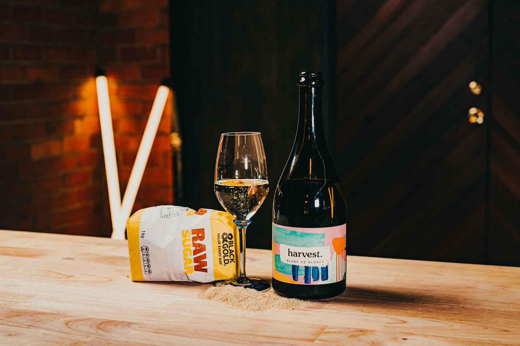 sugar and wine. a bottle sparkling wine and a bag of raw sugar