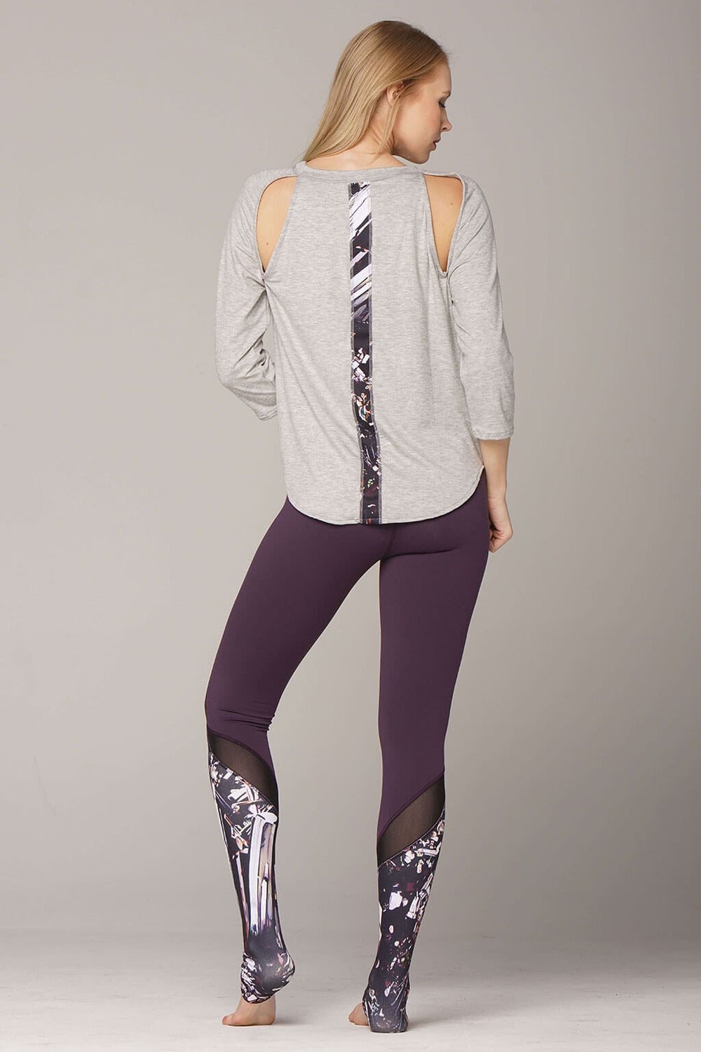 Back view of epidote B-line raglan in grey and matching leggings with art stripe down back and
