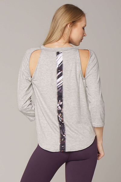 Back view of epidote B-line raglan in grey with art stripe down back and