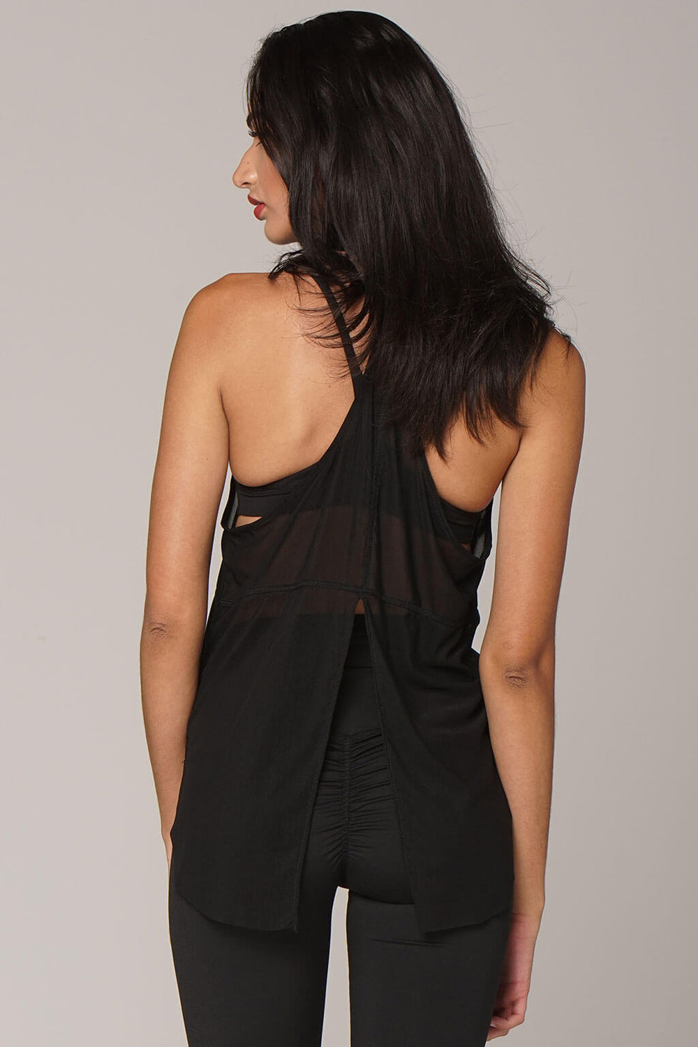 Back view of yogavated muse mesh tank top in black with slit from bottom up half way in center back