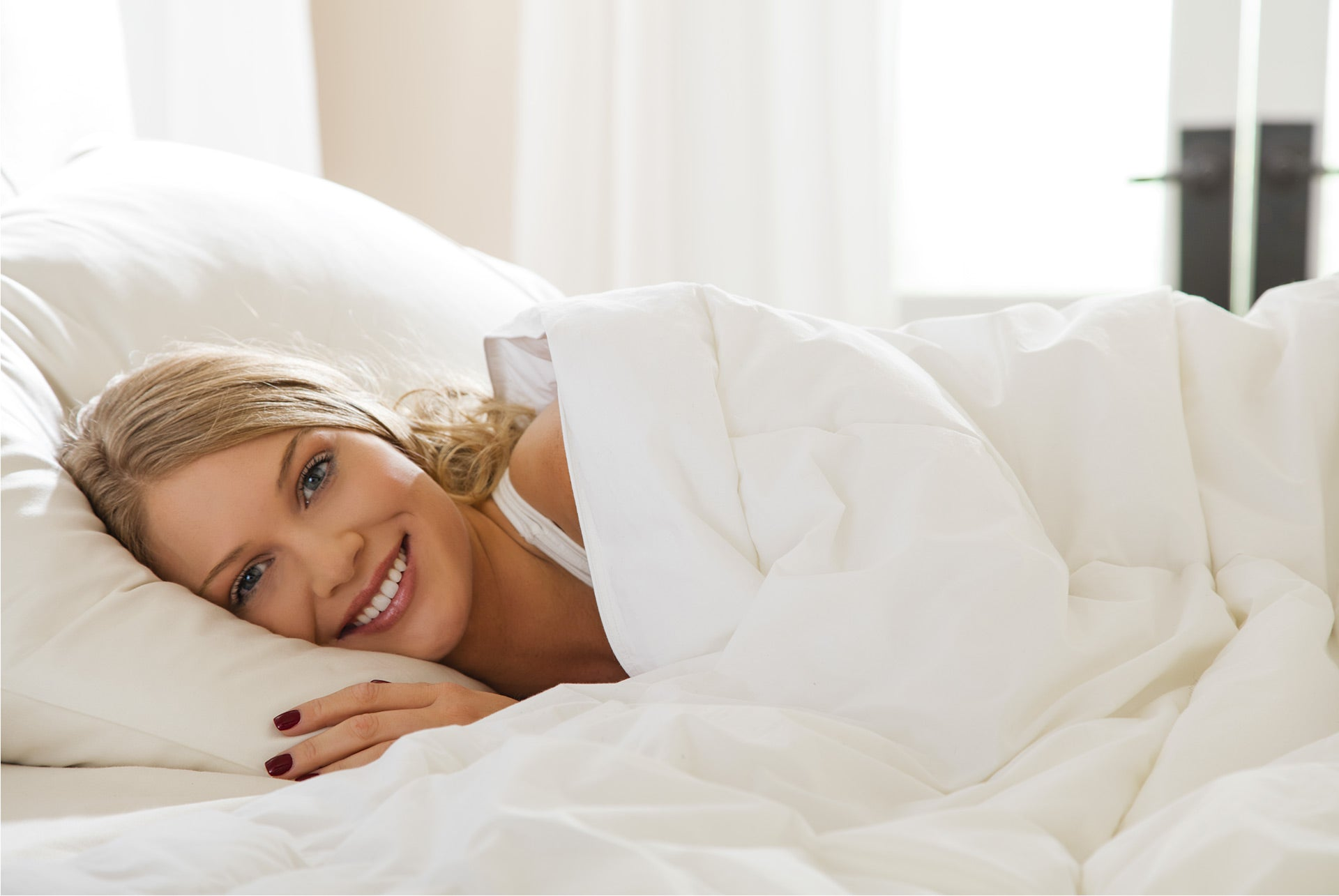 woman lying happily, smiling in bed
