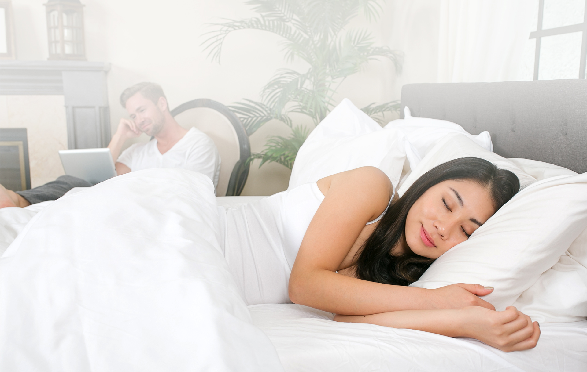 woman sleeping peacefully in bed, man reading beside bed