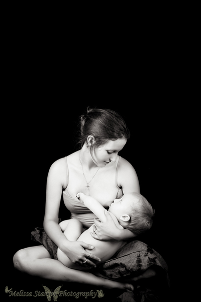 Mother breastfeeding baby black background black and white in studio