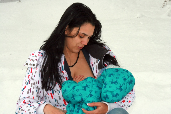 Mother breastfeeding baby in cold weather