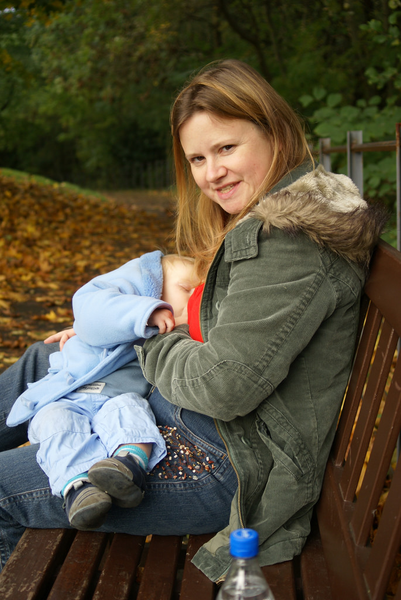 Mother breastfeeding baby on a park bench
