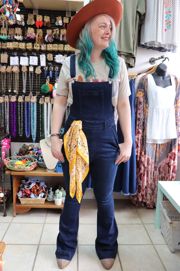 Our two favorite things combined into one! A super soft dark denim flare jean made into overalls. Complete with belt loops and a side zipper closure, as well as adjustable shoulder straps.  Style Suggestion: Pair with a bell sleeve top while it's still cold or a cute tank for the springtime. Perfect for a one-of-a-kind outfit for Rodeo! Size Suggestion: Small (2-4), Medium (6-8), Large (10-12), X-Large (14-16)