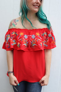 Who's ready to fiesta? This embroidered fiery red top is perfect for a fiesta any day! Complete with elastic for the perfect stretch across your shoulders, and our favorite: colorful embroidered detail across the front.  Style Suggestion: Pair with some distressed shorts or our flare jeans for an outfit perfect for the rodeo or summertime! Size Suggestion: Small (2-4), Medium (6-8), Large (10-12)