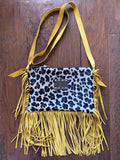 "Available in a variety of fringe colors and fur patterns, this bag is perfect for everyday use and fits exactly what you need for a day or night out.  -Made of authentic leather -Lined with a zipper closure 12""x8"" Crossbody Strap 26"""