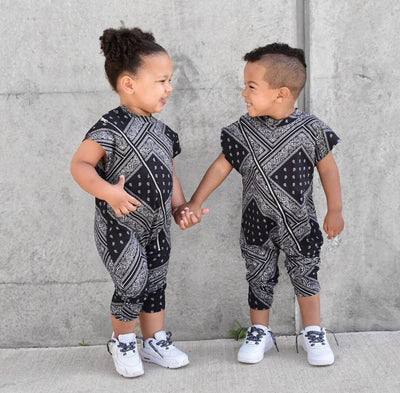 Little boy and girl wearing matching bandana print rompers